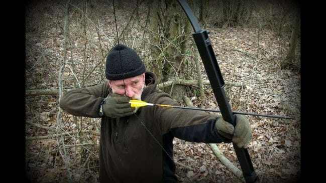 a man shooting with a survival bow and an arrow rest